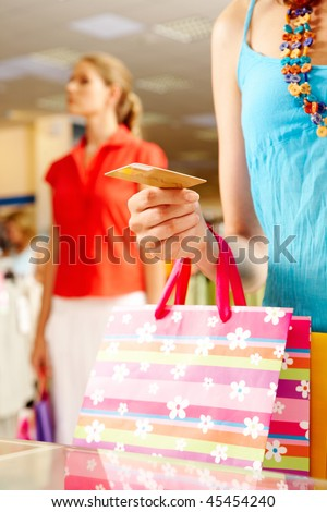 Close-up of woman?s hand holding plastic card while going shopping in the mall - stock photo