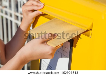 Close-up of woman's hand inserting envelope in mailbox - stock photo
