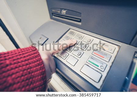 Close-up of woman's hand pushing button on atm.Unrecognizable - stock photo