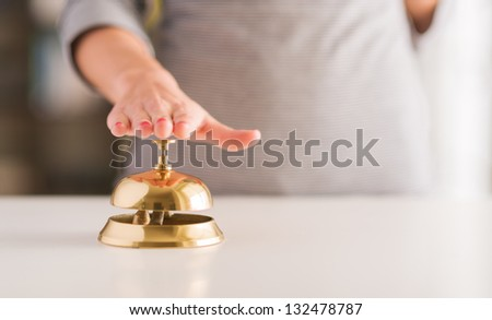 Close-up Of Woman's Hand Ringing Service Bell - stock photo