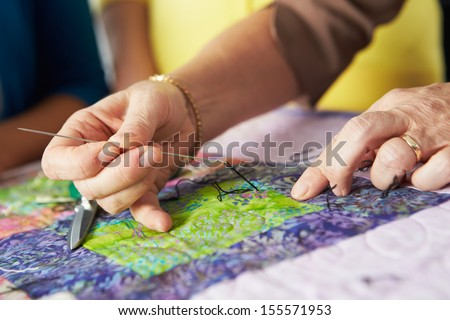 Close Up Of Woman's Hand Sewing Quilt - stock photo