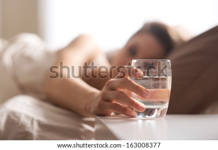 Close up of woman's hand taking a glass of water - stock photo