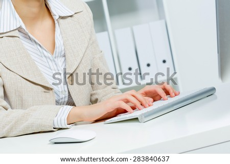 Close up of woman's hands working in office on computer - stock photo