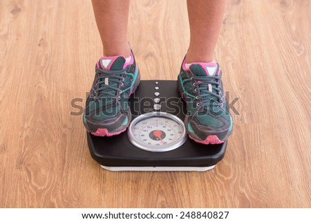 Close-up of woman's legs on the scales. - stock photo