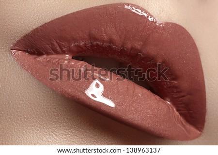 Close-up of woman's lips with fashion natural brown lipstick makeup. Horizontal macro sexy pale lipgloss make-up - stock photo