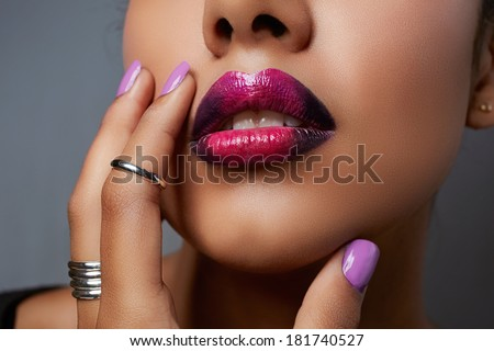 Close-up of woman's mouth with dark fashion purple lipstick with ombre effect. Hand with purple nailpolish touching tanned face - stock photo