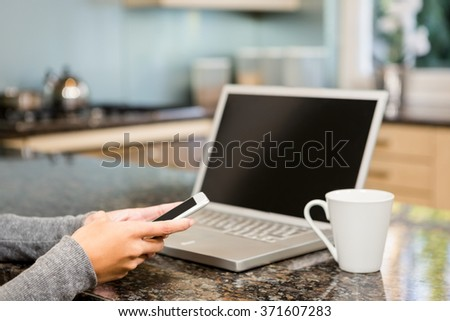 Close up of woman using smartphone and laptop in the kitchen - stock photo