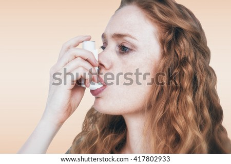 Close-up of woman using the asthma inhaler against orange background - stock photo