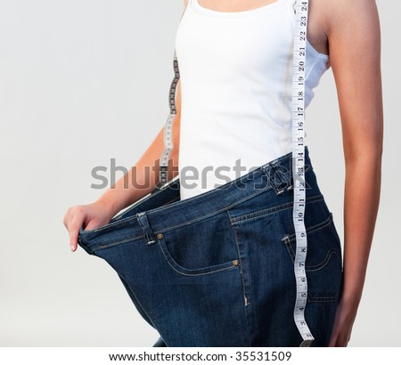 Close-up of woman wearing big jeans after weight loss with focus on woman - stock photo