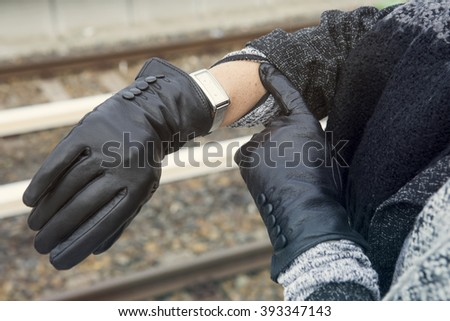 close-up of woman wearing gloves looking at her watch at train station - stock photo