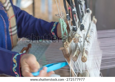 Close up of  woman weaving white pattern on loom in Chiang Mai Thailand - stock photo