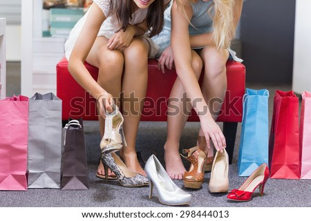 Close up of women trying on shoes in shoe shop - stock photo