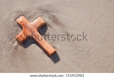 Close up of wood carved cross on beach - stock photo