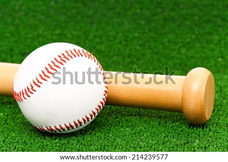 Close-up of wooden bat and baseball ball on artificial green grass - stock photo