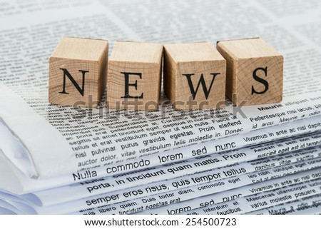 Close-up Of Wooden Blocks Spelling News On Stack Of Newspapers - stock photo