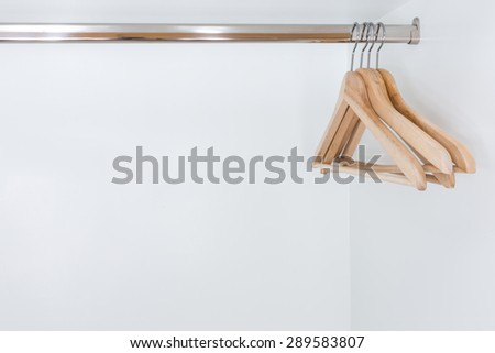 close up of Wooden clothes hanger in white wardrobe - stock photo
