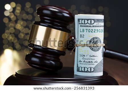 Close-up Of Wooden Gavel With Rolled Banknote Tied With Rope - stock photo