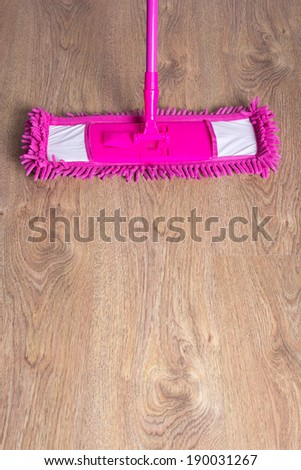 close up of wooden parquet floor with pink cleaning mop - stock photo