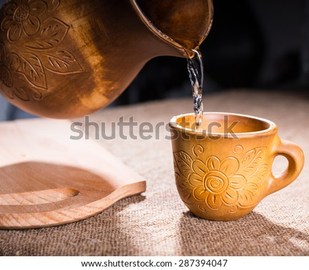 Close Up of Wooden Pitcher Pouring Water into Drinking Cup Both Carved with Floral Pattern Design on Table with Cutting Board - stock photo