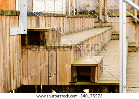 Close up of wooden seats for spectators with some fenced railing in front. Closest is a simple staircase to walk up and down on to get to the seats below. - stock photo