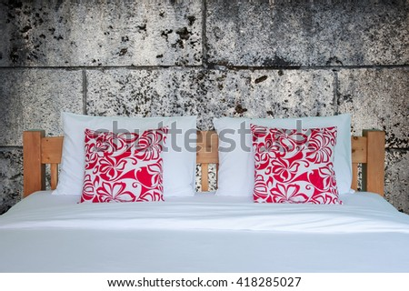 Close up of wooden white bedding sheets and red pillow on cement wall  - stock photo