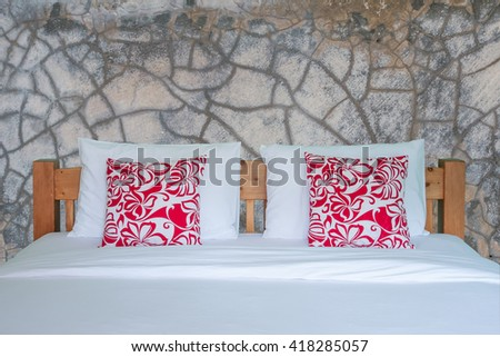 Close up of wooden white bedding sheets and red pillow on grungy gray cement - stock photo