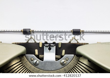 Close-up of word donate on white sheet in typewriter - stock photo