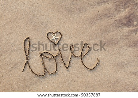 close up of word 'love' written in sand at beach - stock photo