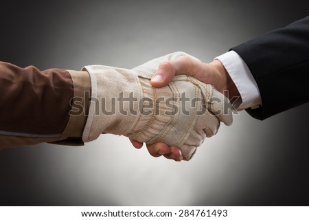 Close-up Of Worker Wearing Glove Shaking Hand With Businessman - stock photo