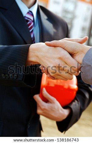 Close-up of worker with helmet handshaking with businesswoman - stock photo