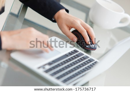 Close-up of working businesswoman. Woman's hands touching computer mouse and keys of silver opened laptop. Focus on hand and computer. - stock photo