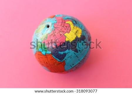 Close up of world globe - top view - travel destination and love different cultures concept - place for text - on pink background - stock photo