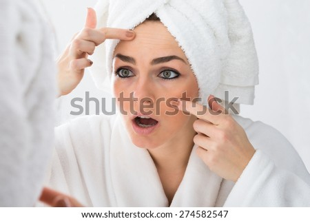 Close-up Of Worried Woman Looking At Pimple On Face In Mirror - stock photo