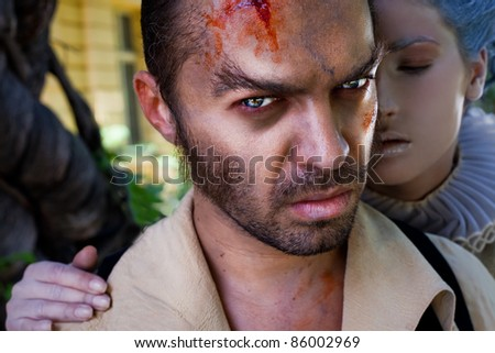 Close-up of wounded male vampire looking at camera, medieval woman embracing him - stock photo