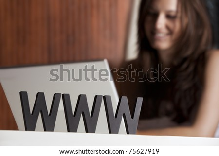 Close-up of www letters in front of smiling young woman sitting at laptop, symbolizing internet surfing. - stock photo