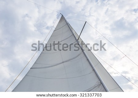 Close up of yacht mast and sail on sky background. Sailing boat part. - stock photo