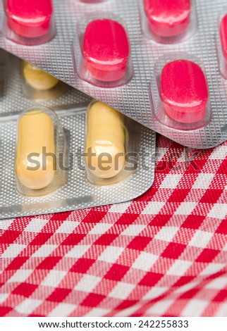 Close up of yellow capsules and red pills in blisters - stock photo