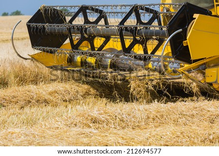 Close-up of yellow harvester on a grain field. - stock photo