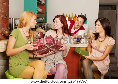 close-up of young attractive caucasian girls sitting against the counter in a cafe exchanging presents, with a handsome guy behind the counter holding an engagement ring in a box - stock photo