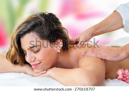 Close up of young attractive woman enjoying back massage. Therapist hands massaging shoulders and neck. - stock photo