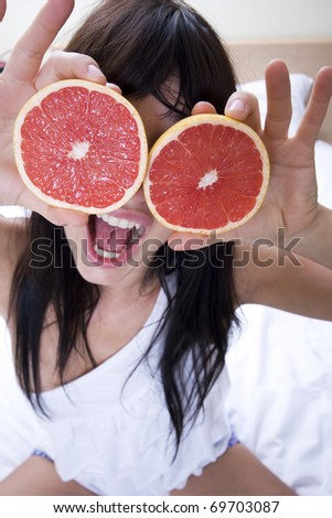 close up of young attractive woman playing with grapefruit - stock photo
