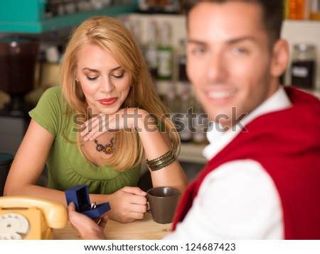 close-up of young beautiful caucasian girl being overwhelmed by a marriage proposal in a cafe - stock photo