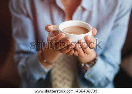 Close up of young beautiful unrecognizable woman hands holding hot cup of coffee or tea with milk - stock photo