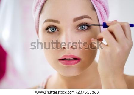 Close up of young beautiful  woman applying mascara - stock photo