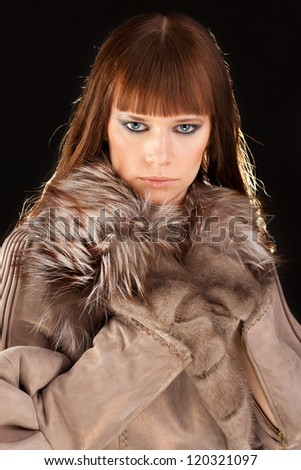 Close-up of young beautiful woman with stylish make-up and fur - stock photo
