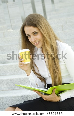Close-up of young business woman with a green folder and a paper cup of coffee - stock photo