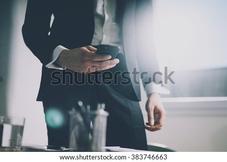 Close up of young businessman in black suit using smart phone while staying at his office, filtered image, male hands with cell phone - stock photo