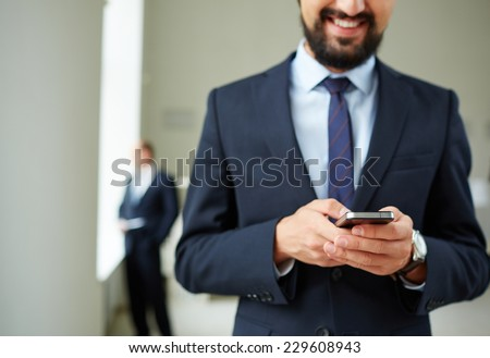 Close-up of young businessman using cellular phone on background of his colleague - stock photo