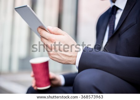 Close up of young businessman with new tablet and coffee - stock photo
