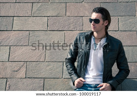 Close up of Young casual man portrait against wall. - stock photo